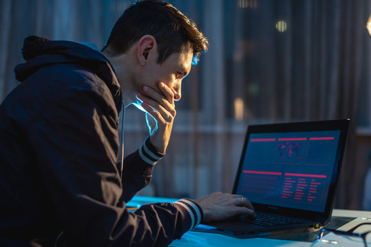 Male hacker thinking about the problem of hacking and stealing access databases with passwords. Concept of cybersecurity