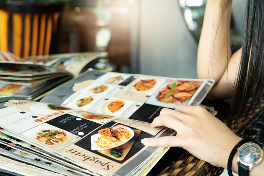 young women looking menu at restaurant, selective focus on menu