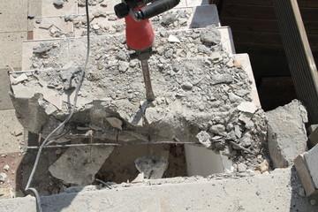 mit einem Abbruchhammer eine alte Treppe abreißen