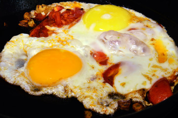 Aluminium Prints Egg Fried eggs with colorful yolks and tomatoes. In the form of the artist's palette. Fried on a black cast iron skillet.