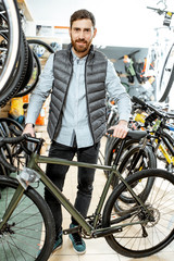 Portrait of a handsome man as a buyer or salesperson with bicycle at the bicycle store