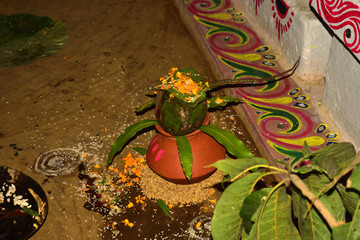 earthen pot and mango leaves with floral decoration