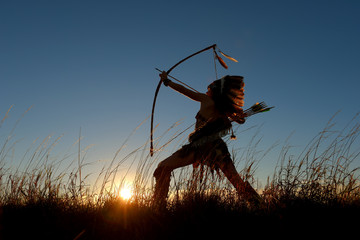 A young girl plays the part of a native American Indian girl. She poses proudly in a grassy field in the prairie The girl is silhouetted as the sun sets behind her.