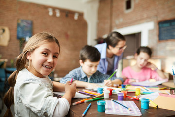 Portrait of cute little girl looking at camera while enjoying art class with group of children, copy space
