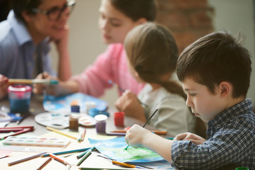 Side view portrait of cute little boy painting pictures in art class with group of children, copy space