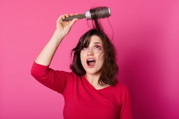 Adorable woman with brown tangled hair tries to comb hairs, looks up, wants to blow out comb and doing new hairstyle, dressesd in casual jumper, poses against pink wall, copy space for advertisment.