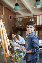 Portrait of smiling boy painting picture on easel in art class and holding palette, copy space