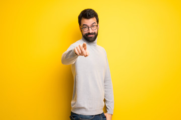 Man with beard and turtleneck points finger at you with a confident expression Wall mural