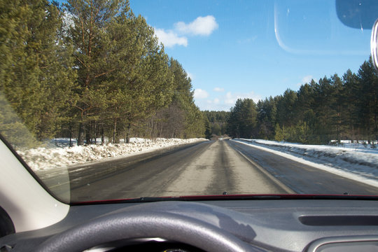 View of the road through the windshield. Snow on the sidelines. Wet asphalt road. Blue sky with clouds. Point of view of the driver looking through the windshield of the car.