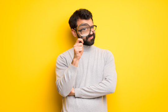 Man with beard and turtleneck taking a magnifying glass and looking through it