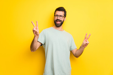 Man with beard and green shirt smiling and showing victory sign with both hands