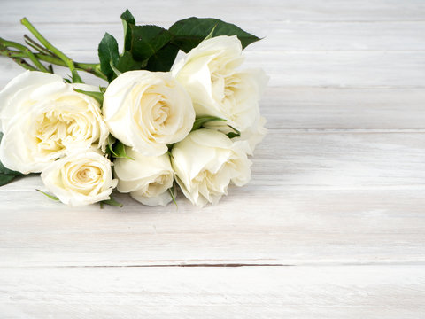 White roses on a white wooden table