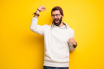 Hippie man with dreadlocks celebrating a victory