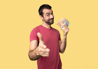 Man taking a lot of money shaking hands for closing a good deal on isolated yellow background