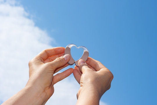 Woman's hands showing heart with hearing aids in front of natural blue sky