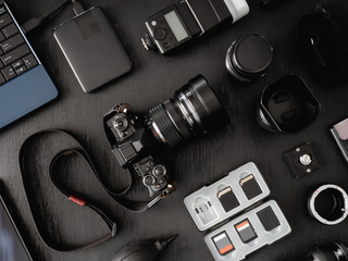 top view of work space photographer with digital camera, flash, cleaning kit, memory card, external harddisk, USB card reader, laptop and camera accessory on black table background.
