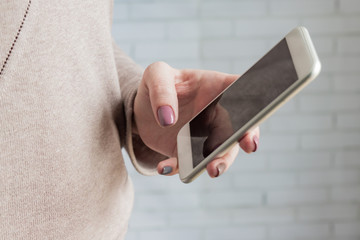Woman holding white smatphone in her hand with trendy manicure. Selective focus