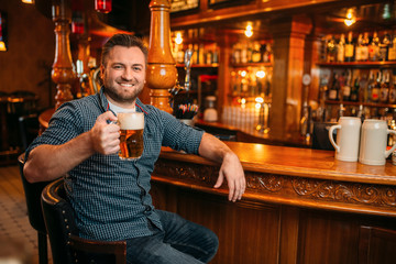 Cheerful man with beer mug at the counter in pub