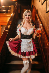 Sexy waitress with mug of beer on the stairway