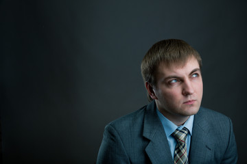 Young pensive businessman on black background