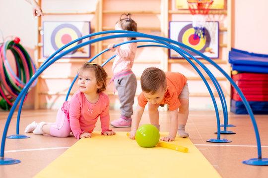 Nursery babies playing together in kindergarten gym