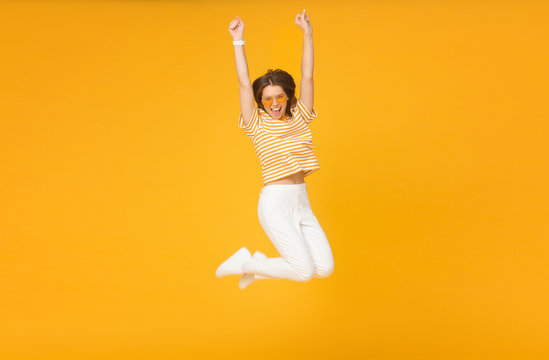 Cheerful positive girl jumping in the air with raised fists if she is winner, isolated on yellow background
