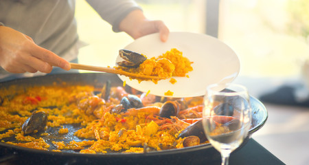 Paella. Traditional spanish food. Person putts seafood paella from the fry pan to plate. Paella with with mussels, king prawns, langoustine and squids