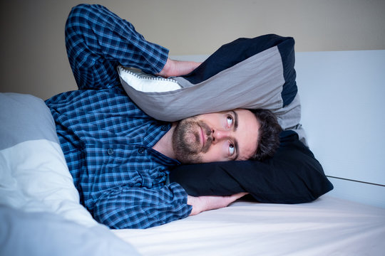 Night noise and man suffering insomnia in bed