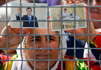 A woman holds pictures of jailed former leader of Turkey's main pro-Kurdish Peoples' Democratic Party Selahattin Demirtas as people gather to celebrate Newroz, which marks the arrival of spring and the new year, in Istanbul