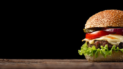Homemade hamburger close-up with beef, tomato, lettuce, cheese and onion on wooden table. Fastfood on dark background