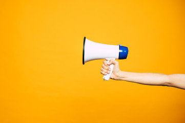 In a bull voice. A yellow background with a woman's hand in front of it holding three colored  megaphone of white, black and blue colors. Fototapete