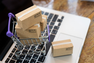 Paper boxes in a trolley on a laptop computer ,Easy shopping online concept,Online shopping or ecommmerce concept