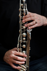 Fototapete - The hands of a musician playing the bass clarinet