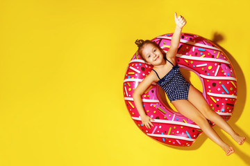 Little girl in a bathing suit, lying on a donut inflatable circle. A child shows thumbs up. Yellow background. Top view. Summer concept.