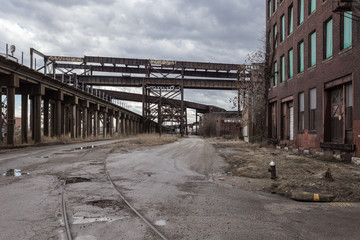 Crossing elevated train tracks and vintage red brick abandoned factory