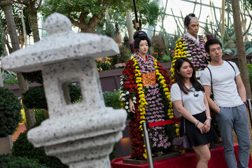 Visitors pose in front of mannequins dressed in chrysanthemums in the likeness of Japanese traditional attire during the Sakura Matsuri Floral Display at Gardens by the Bay in Singapore