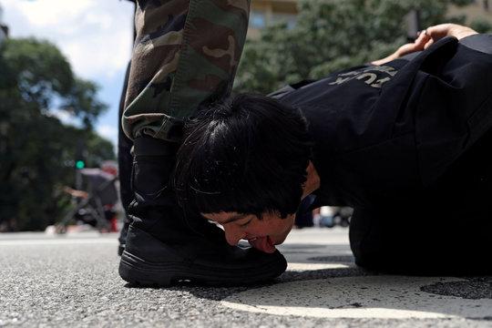 "Venezuelan artist Deborah Castillo licks the boots of a man during her performance ""Lamebrasil, Lamezuela - questioning power in Latin America,"" in Sao Paulo"