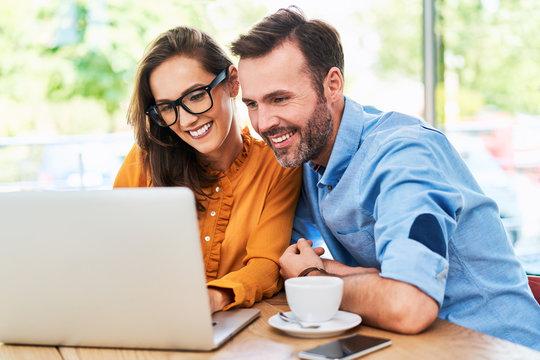 Happy couple using laptop at cafe enjoying time together