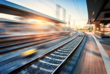 Photo sur Aluminium Voies ferrées Railway station with motion blur effect at sunset. Industrial landscape with railroad, blurred railway platform, sky with orange sunlight in the evening. Railway junction in Europe. Transportation