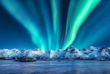 Photo sur Aluminium Aurore polaire Aurora borealis above the snow covered mountains in Lofoten islands, Norway. Northern lights in winter. Night landscape with polar lights, snowy rocks, reflection in the sea. Starry sky with aurora