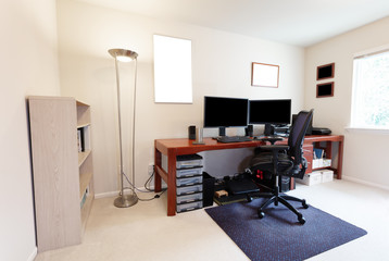 Computer chair at large work table with computer monitors and other technology equipment in bright home office interior