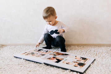 Cute baby sitting and looking at a large stylish photo book with their photos. Children's photo album