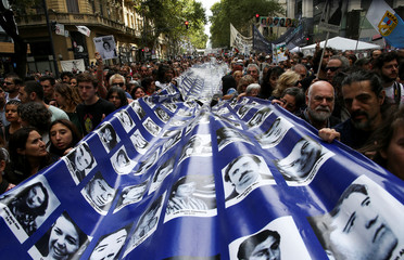 Demonstrators hold a flag with images of people who disappeared, during the march towards Plaza de Mayo square to commemorate the 43rd anniversary of the 1976 military coup, in Buenos Aires