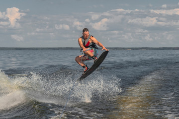 Tense man wakeboarding in a lake and pulled by a boat. Jumping from wave Wall mural