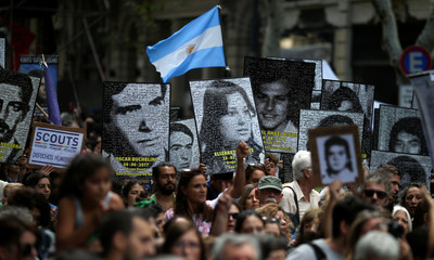 Demonstrators hold images of people who disappeared, during the march towards Plaza de Mayo square to commemorate the 43rd anniversary of the 1976 military coup, in Buenos Aires