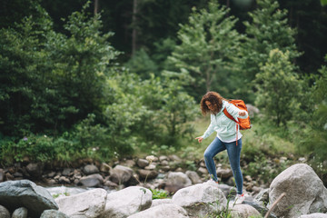 Beautiful woman hiker with backpack near wild mountain river