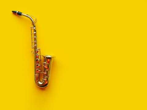 Saxophone on bright yellow background. Wind musical instruments. Copy space for the text