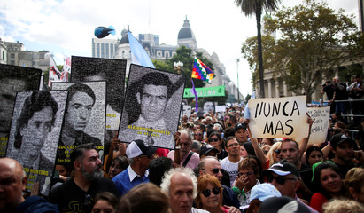 Demonstrators hold images of people who disappeared at the Plaza de Mayo square to commemorate the 43rd anniversary of the 1976 military coup, in Buenos Aires