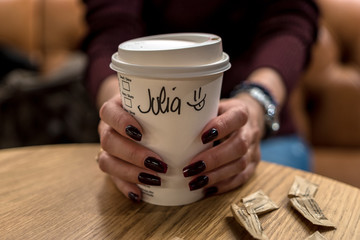 Cup of coffee with writen word JULIA in woman hand.