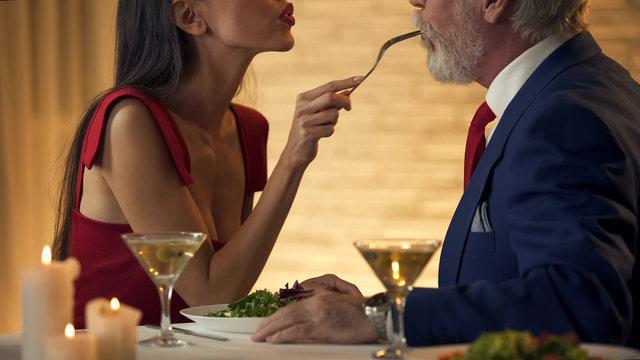 Elegant woman feeding old boyfriend restaurant, dating affection, couple in love